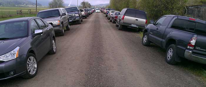 Probably 200 cars parked on this narrow dirt road