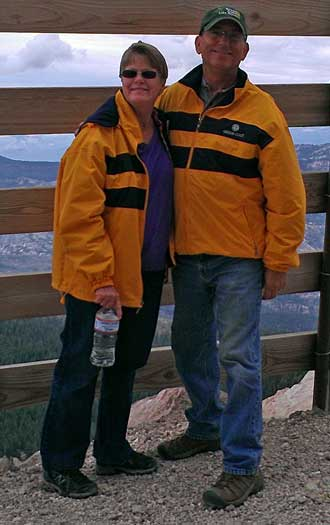 Dale and Gwen and the top in matching Oregon Coast jackets; Behind: Trail map of Mammoth Mountain bicycle trails