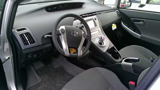 The cockpit of the Toyota Prius, Behind: Salesman, Cody, runs to the office for a license before a test drive.