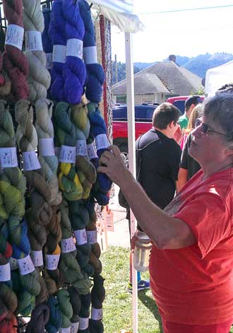 Carole inspect yarn while Jack and I look at the car show, Behind: Lots of shopping booths