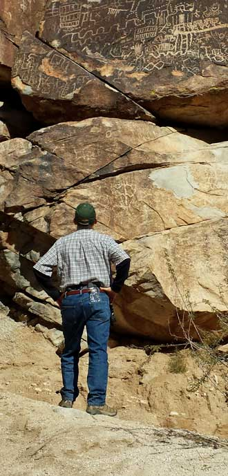 I examine some canyon petroglyphs, Behind: at larger view