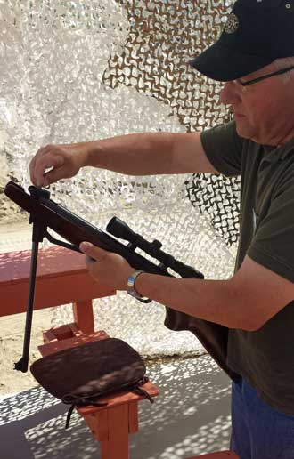 Bill teaches me how to load a pellet rifle, Behind: view of the air-gun range