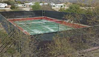 A single tennis court, Behind: miniature golf