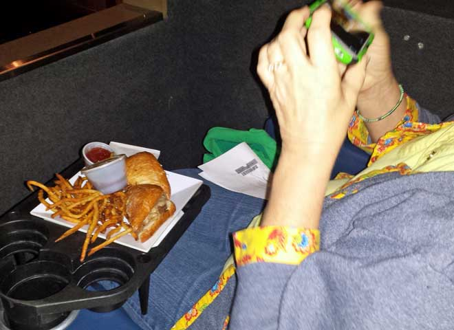 Gwen's meal tray, Behind: the leather seats on the theater floor