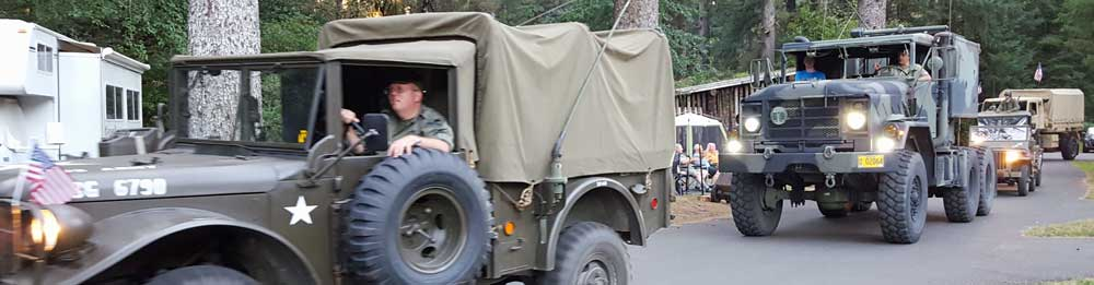 Antique military vehicles are paraded through Forth Stevens State Park