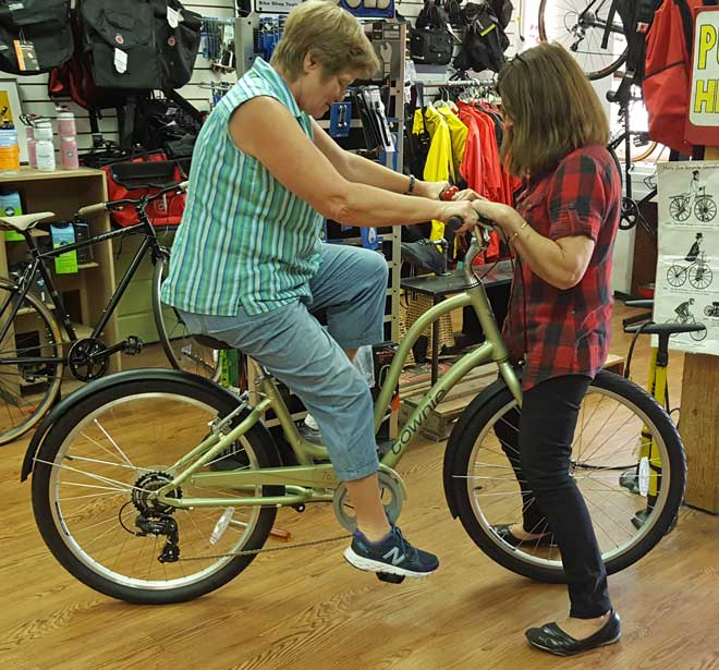 Gwen is checking the seat height with Susan, the Blue Heron Bike Shop owner