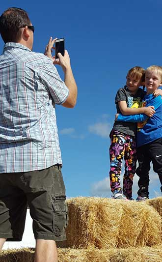 Playing on the hay stack at the pumpkin patch