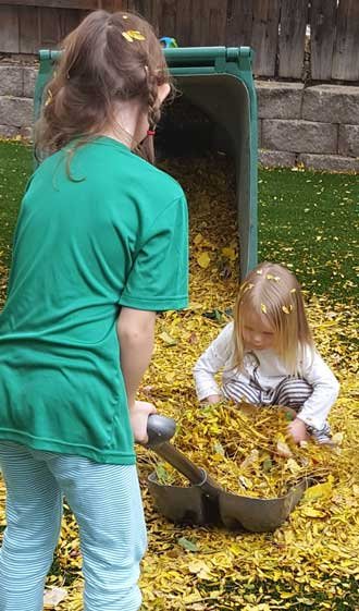 Chloe and cousin Lucy helping dad with the leaves
