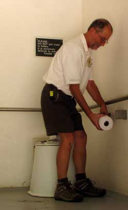 Dale adding rolls of toilet paper in a pit toilet room
