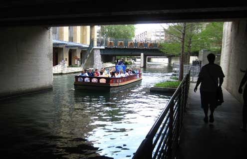 Walking the San Antonio Riverwalk with a river barg passing by.