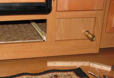 The copper tubing ends under the refrigerator