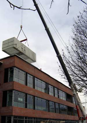 The heating and AC unit is hoisted to the roof